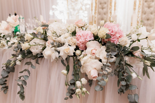 Decorative floral composition on the table made of fresh eucalyptus, roses and hydrangea