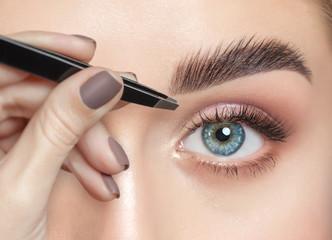 Make-up artist plucks eyebrows with tweezers to a woman with curly brown hair and nude make-up....