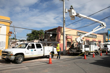 Workers fix power lines after the earthquake in Guayanilla