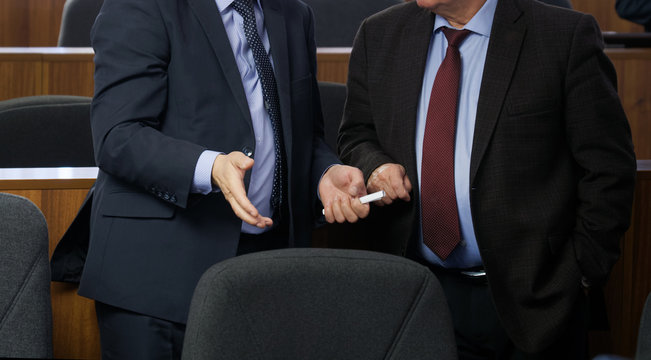 Two politicians or businessmen are talking to each other before the start of a meeting or conference. Discussion of the pressing issues of our time. Preparing for a decision