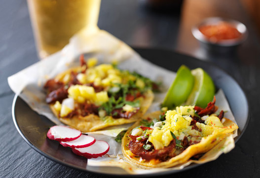 al pastor street tacos with pineapple, radish and beer