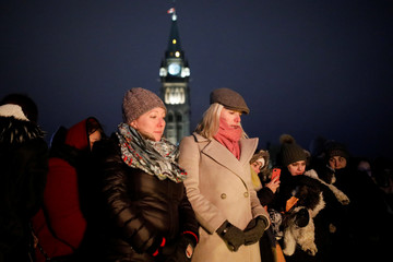 Canada's Minister of Middle Class Prosperity Mona Fortier and Minister of Infrastructure and Communities Catherine McKenna attend a candle light vigil for the victims of Ukraine International Airlines flight PS-752 on Parliament Hill in Ottawa