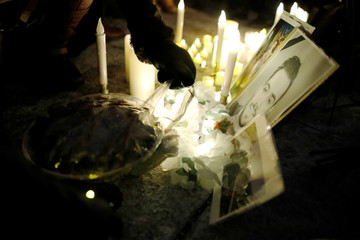 An attendee unwraps a plate of food at a candle light vigil for the victims of Ukraine International Airlines flight PS-752 on Parliament Hill in Ottawa