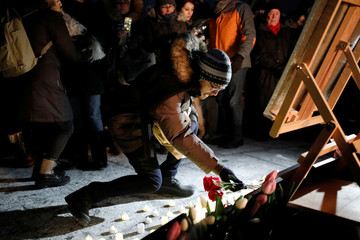An attendee places flowers at a candle light vigil for the victims of Ukraine International Airlines flight PS-752 on Parliament Hill in Ottawa