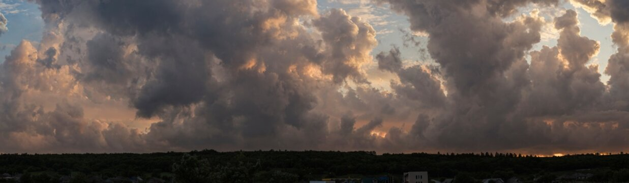 Leaden, storm clouds covered the sunset. Cumuliform cloudscape on blue sky. The terrain in southern Europe. Fantastic skies on the planet earth. Tragic gloomy sky..