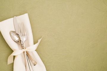 Table Place Setting with Silverware and White cloth napkin on Light Olive Green Brocade Tablecloth as the background with copy space.  It's a Horizontal with Above View.