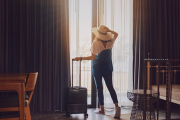 Asian women are staying in a hotel room with luggage.Open the curtain and  door in the room looking to outside view.Travel in holidays concept.Vintage tone.