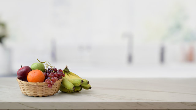 Cropped shot of fruit basket and copy space on marble desk with blurred kitchen room