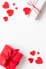 Present to a lover on Valentine's Day. Gift boxes near paper hearts on white background top-down...