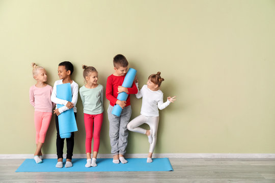 Little children with yoga mats near color wall in gym