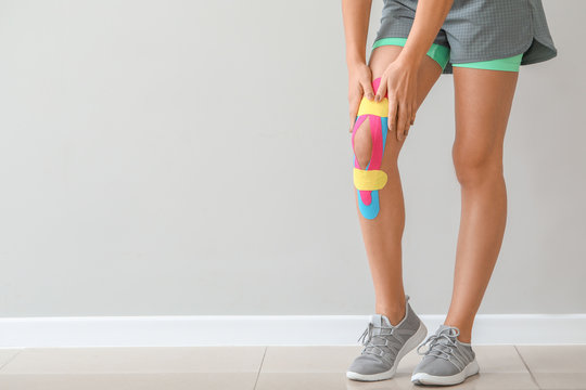 Sporty woman with physio tape applied on knee against light background