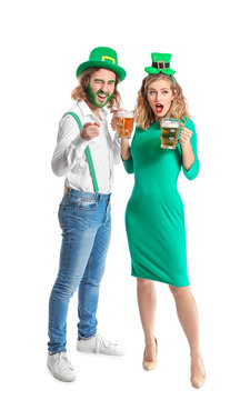 Young couple with beer on white background. St. Patrick's Day celebration