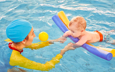 Young mother aged 30 years and baby son of 5 months are in pool. Smiling woman with beautiful snow-white smile is dressed in fashionable swimming suit swimsuit and cap. Girl teaches boy to swim.