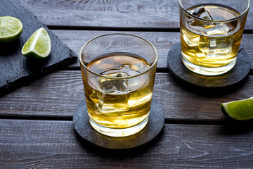 Canvas Prints Bar Whiskey with ice. To glasses of strong alcohol drink near lime on dark wooden background