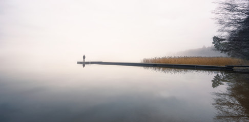 Man standing alone on edge of pier and staring at lake. Mist over water. Foggy air. Early chilly...