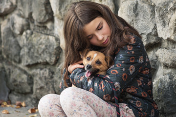 beautiful teen girl hugging her new pet adopted friend  dog from rescue shelter