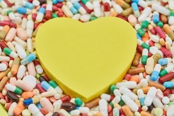 Gelbes Herz mit vielen Medikamenten