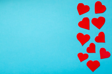 Valentine day concept. Red decorative hearts on blue background. Free space for your text.