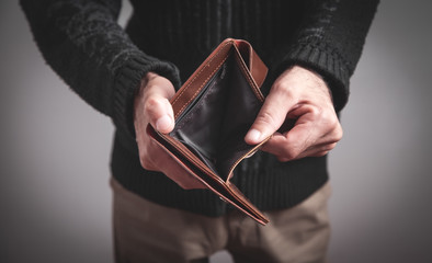 Man holding empty wallet. No money