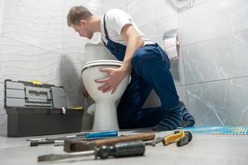 man plumber in uniform installing toilet bowl using instrument kit professional repair service Fotobehang