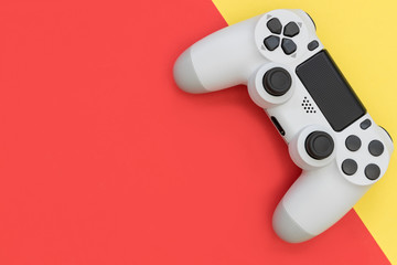 Video game gaming controller on bright red yellow color background top view