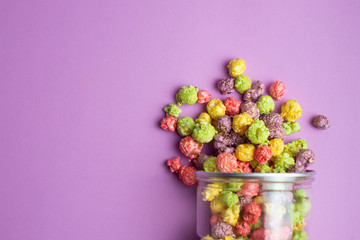 Multicolored fruit flavored popcorn in glass cups on pink background. Candy coated popcorn. Wall mural