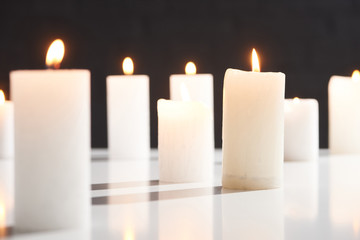 selective focus of burning white candles on white surface glowing isolated on black