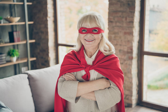 Close-up portrait of her she nice attractive cheerful cheery gray-haired lady wearing red costume super nanny planet save rescue service folded arm at industrial brick loft modern style interior house