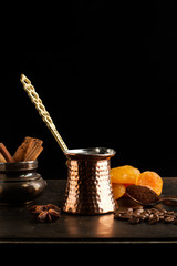 Cafetera Turca y Café en granos y molido sobre fondo oscuro con albaricoques, canela y anís estrellado.. Vista de frente