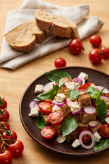 Photo sur Aluminium Fleur selective focus of delicious Italian vegetable salad panzanella served on plate on wooden table near fresh tomatoes and bread