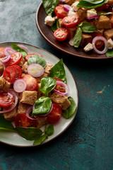 Photo sur Aluminium Fleur fresh Italian vegetable salad panzanella served on plates on table