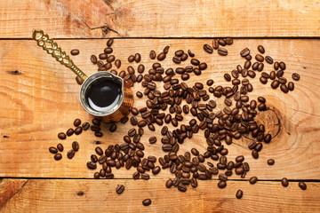 Cafetera Turca con café y café en granos sobre mesa de madera rústica. Vista superior