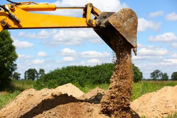 Yellow excavator shovel digging pit in ground