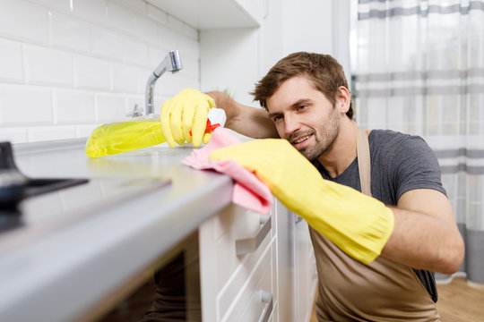 Close-up of young man in yellow gloves using cleanser to wash kitchen furniture