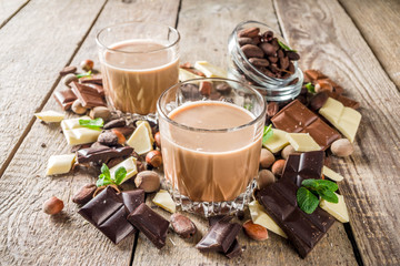 Sweet and strong alcohol drink. Chocolate liqueur with milk and dark chocolate pieces. Wooden background copy space