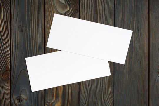 Two blank cards or papers (business cards, tickets, flyers, invitations, coupons, banknotes, etc.) on dark wooden background