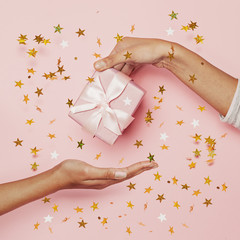 Blowing gold confetti stars glitter, gift and two female hand on pink background. Holiday...