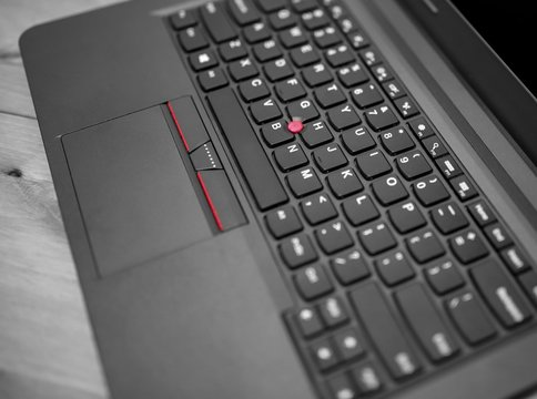 Black laptop keyboard trackpoint red dot cap and touchpad with buttons close up view