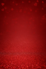 Sparkling deep red glitter background with hearts. Abstract background for Valentine's Day, love and romantic celebration. Festive banner and poster. Copy space for text.
