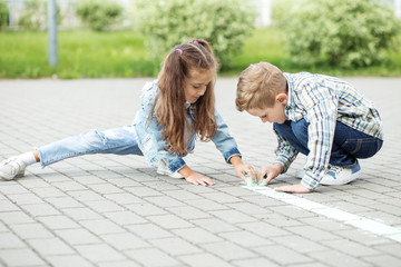 Little girl and boy draw with chalk on the pavement. The concept of childhood, back to school,...