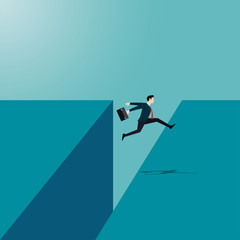 Businessman jumping reach the other side of the cliff