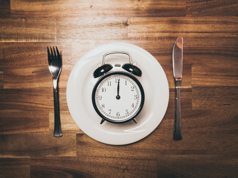 Plate with black vintage Alarm Clock showing Twelve O'clock as symbol for intermittent fasting