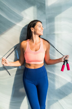 Healthy sports woman in fitness clothes with a jump rope in the modern living room.