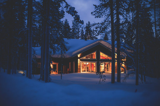 A cozy wooden cabin cottage chalet house covered in snow near ski resort in winter with the lights turn on