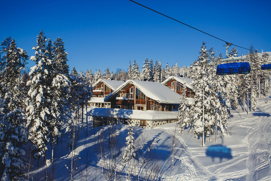 Beautiful vibrant aerial winter mountain view of ski resort, sunny winter day with slope, piste and ski lift