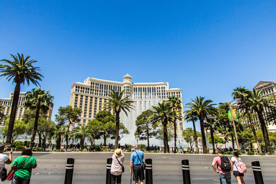 Las Vegas, Nevada - Tourists standing on sidewalk with back to camera talking pictures of the Bellagio Fountains along the Las Vegas strip.