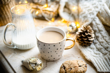 Cozy winter holiday decoration, Christmas lights and coffee cup with decor details, real home