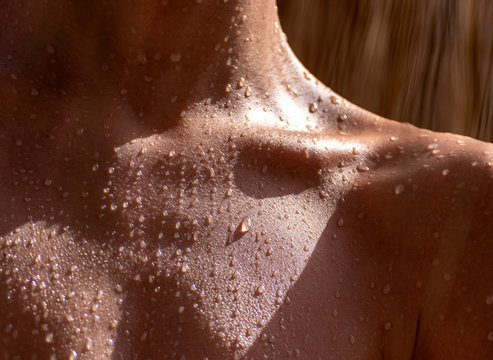drops of sweat on tanned skin, close-up