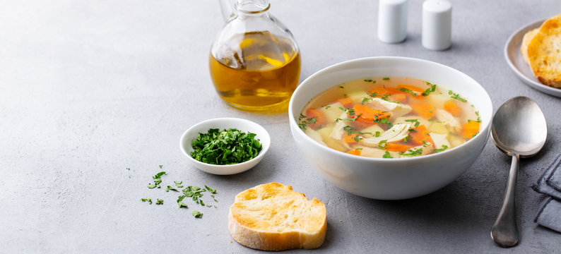 Chicken soup with vegetables in white bowl. Grey stone background. Copy space.