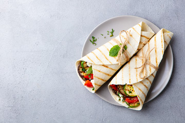 Wrap sandwich with grilled vegetables and feta cheese on a plate. Grey background. Copy space. Top view.